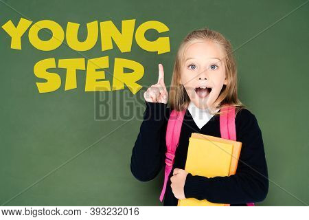 Excited Schoolgirl Holding Book And Showing Idea Gesture While Standing Near Green Chalkboard With Y