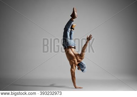 Topless muscualr man in jeans doing a handstand isolated on gray background