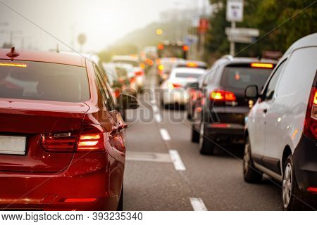 Traffic Jam In A City With Long Queue Of Cars Waiting On A Road At Sunset