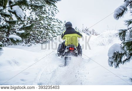 Man Is Riding Snowmobile In Mountains. Pilot On A Sports Snowmobile In A Mountain Forest. Athlete Ri