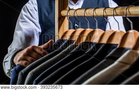 Tailor, Tailoring. Stylish Mens Suit. Male Suits Hanging In A Row. Men Clothing, Boutiques. Man Suit