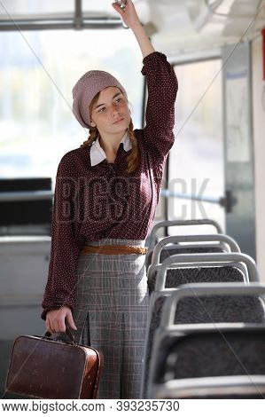 Young Nice Freckled Girl In Retro Style Clothes With A Briefcase Standing In A Wagon Of A Driving Tr