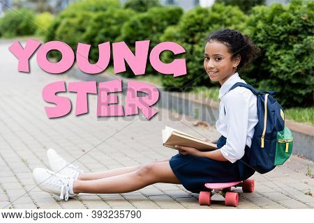African American Schoolgirl Holding Book While Sitting On Penny Board Near Youngster Lettering
