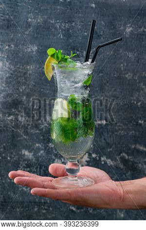 Mojito Cocktail With Lime And Mint In Highball Glass On A Mans Hand, Close-up View Classic Mojito Co