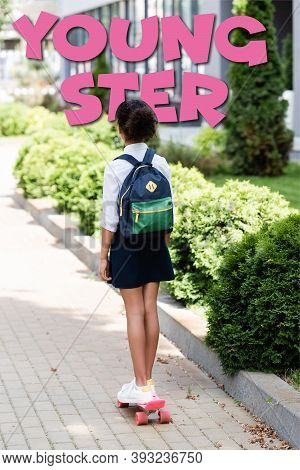 Back View Of African American Schoolgirl With Backpack Riding Penny Board Near Youngster Lettering