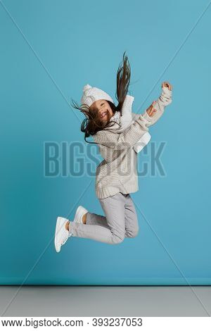 Excited Smiling Cheerful Little Child Girl In White Winter Knitted Hat And Sweater Jumping On Blue B