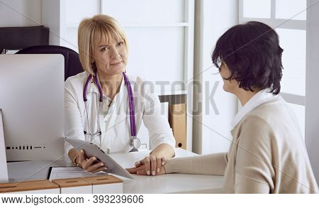 Doctor With Laptop And Pregnant Woman In Doctors Office