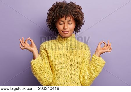 People, Peace And Calmness Concept. Black Young Female Stands In Mudra Posture, Practices Yoga, Medi