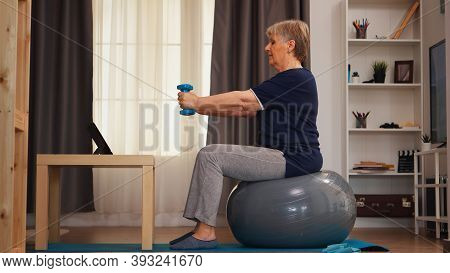Senior Woman Exercising With Dumbbells Watching Online Lesson On Tablet Computer. Online Training Le
