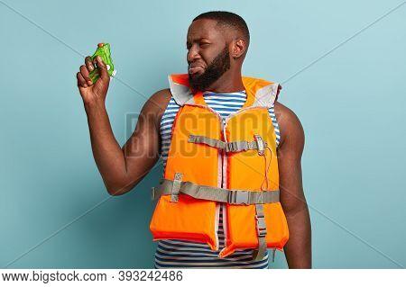 Dejected Sad Dark Skinned Unshaven Man Lost Fight Game, Holds Water Gun, Has Battle Near Sea, Wears