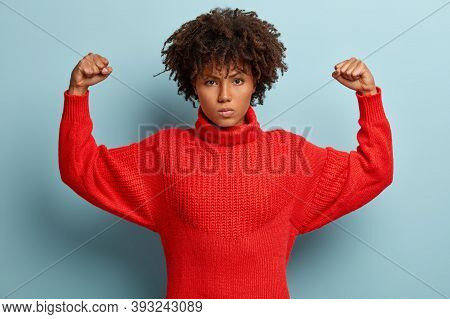 Photo Of Angry Furious Afro American Woman Keeps Arms Raised, Clenches Fists, Shows Muscles, Demonst