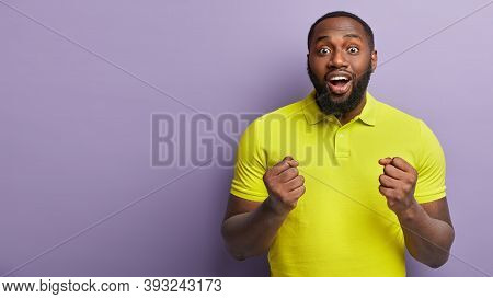 Positive Joyous Glad Young Man Keeps Eyes Widely Opened, Hands Clenched In Fists, Wears Yellow Brigh