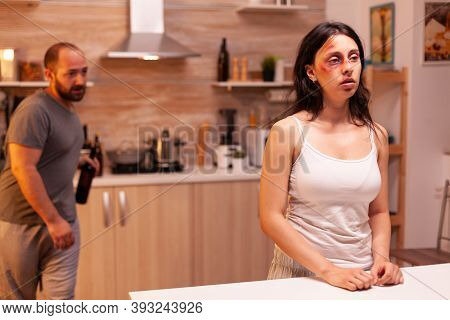 Woman Being Victim Of Domestic Violence From Alcoholic Husband. Violent Aggressive Man Abusing Injur