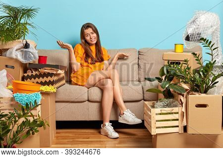 Confused Unhappy Woman Moves In New House, Spreads Hands, Doesnt Know From What To Start Unpacking B