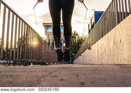 Active Young Woman Jumping With Skipping Rope Outdoors. Sunset Light On Background, Beautiful Perspe