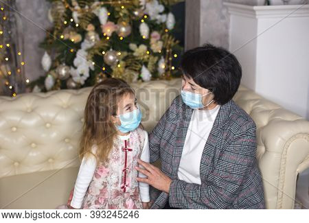 Grandmother And Granddaughter On The Sofa In The Living Room With Christmas Decor Hugging In Medical