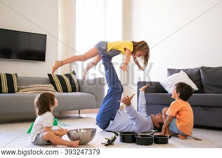 Happy Father Holding Daughter On Legs And Lying On Carpet. Cheerful Caucasian Children Playing In Li
