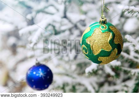 Christmas Tree Toys On The Branches Of A Fir Tree Covered With Snow. Green End Blue Shiny Round Toy