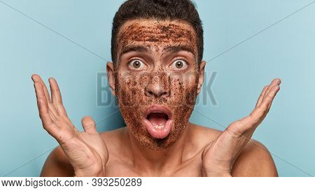 Excited Young Man With Anti Age Scrub Mask, Stares With Omg Facial Expression, Clasps Hands Near Fac