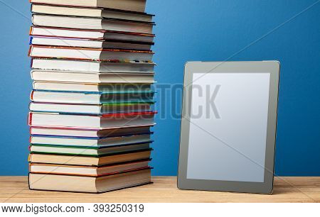 Stack Of Paper Books And An E-book. The Concept Of Replacing Books With Electronic