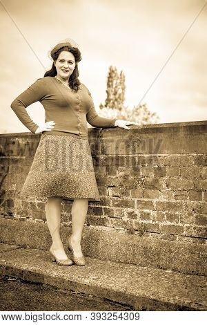 Beautiful Young Woman Posing In Vintage 1940s Clothes, Standing On A Bridge, In Sepia