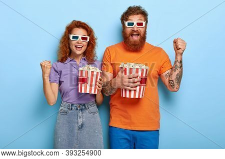 Ginger Happy Couple Rejoice Being In Cinema, Clench Fists, Enjoy Eating Popcorn In Bucket, Watch New