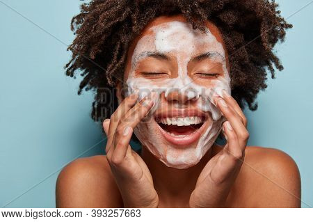 Spa, Therapy And Beauty Concept. Satisfied Black Woman Washes Face With White Soap, Has Cleansing Fo