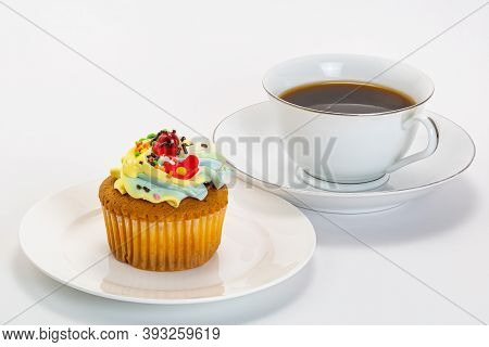 Vanilla Cup Cake Garnished With Butter Cream Frosting And Colorful Sprinkles In White Ceramic Plate