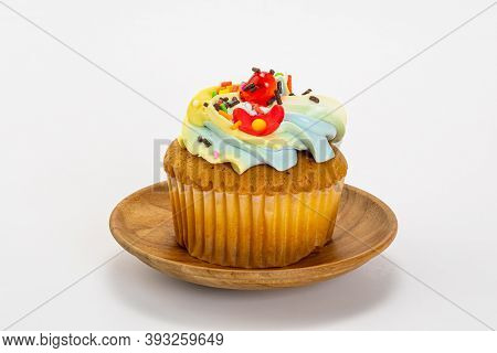 Single Vanilla Cupcake With Butter Cream Frosting Decorate With Multicolored Sprinkles In A Wooden P