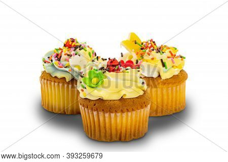 Vanilla Cupcakes Garnished With Colorful Vanilla Butter Cream Frosting And Multicolored Sprinkles On