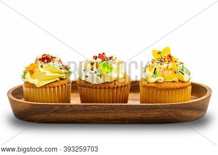 Vanilla Cup Cakes With Colorful Butter Cream Frosting And Multicolored Sprinkles In Wooden Tray On W