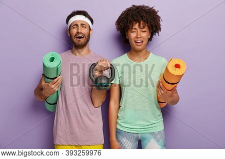 Stressful Diverse Couple Feel Tired After Sport Training With Coach, Hold Fitness Mats, Weight, Dres