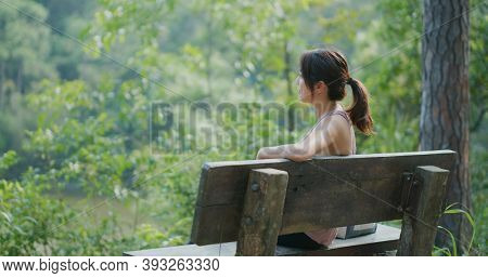 Sport woman look at the lake view and sit on the bench