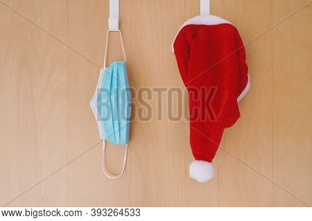 Face Mask And Santa Claus Hat Hanging Side By Side On Over Door Hooks - Christmas During Covid-19 Co