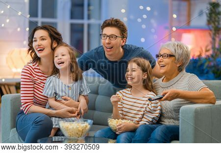 Happy family watching projector, TV, movies with popcorn in the evening at home. Granny, mother, father and daughters spending time together.