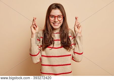 Excited Pleased Female Hopes Finally Dreams Come True, Prays Hopefully With Crossed Fingers, Wears O