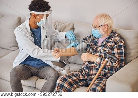 Geriatrician In A Lab Coat Measuring The Blood Tension