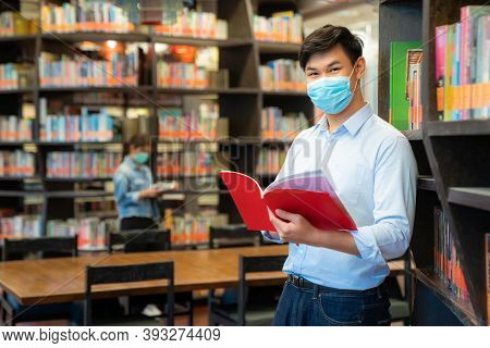 Two Asian University Students Wearing Face Mask And Standing In Library Social Distance From Other 6