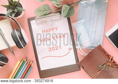 Word Happy New Year 2021 On Clipboard With Stationery, Mask And Hand Sanitizer On Pastel Pink Backgr