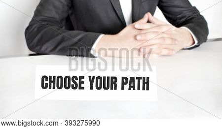 Businessman Sitting At The Table And Signboard With Text Choose Your Path