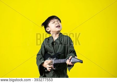 Musician Boy Playing Toy Guitar, Very Fun Gestures On Yellow Background.
