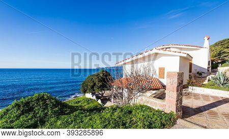 Porto Alabe, Sardinia Island, Italy - December, 12, 2019: Beautiful White Holiday House Aloing The B