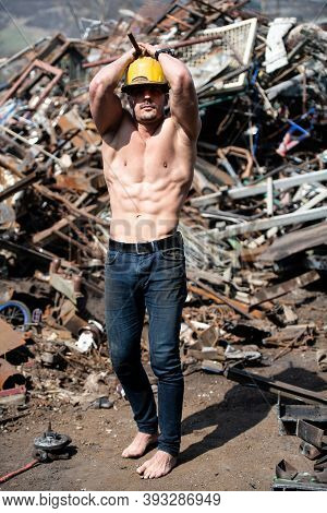 Man With Six Pack In Old Scrap Metal Garage