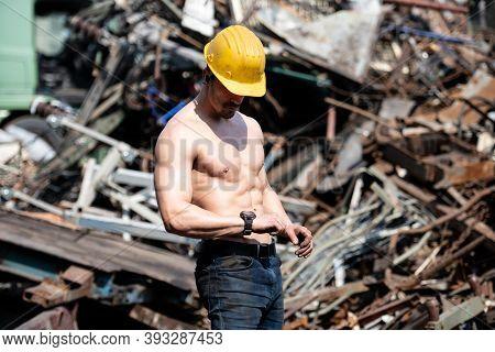 Man Flexing Muscles In Industrial Junk Yard