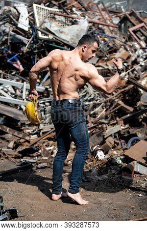Bodybuilder Flexing Muscles Outdoors In Industrial Junk Yard
