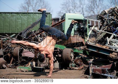 Bodyweight Training Man Standing On Hand In Junkyard