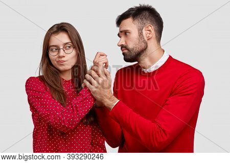 Desperate Young Caucasian Man Holds Hand Of Girlfriend, Looks With Miserable Expression, Asks For Fo