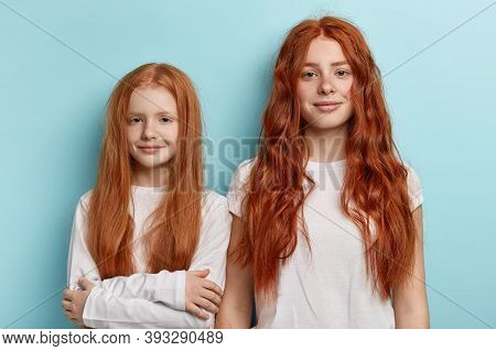 Portrait Of Two Redhaired Sisters In Casual Wear Look At Camera Seriously Stand Closely, Have Good F