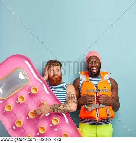 Sorrowful Dejected African Amrican Man Being In Low Spirit, Wears Swimcap With Lifejacket, Curly Red