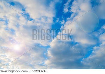 Blue sky background, white dramatic sky fluffy clouds lit by sunset sky light. Vast sky landscape scene, blue sky view. Blue sky background, vast sky landscape, sky scene with dramatic sky clouds.
